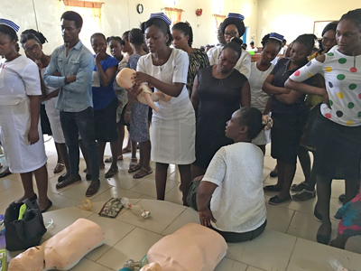 West African nurses watch as one nurse practices infant CPR during a training led by PBA professor Dr. Nakisha Kinlaw. Kinlaw and Dr. Amos Abioye helped train nurses and pharmacists at Egbe Hospital, which serves the needs of about 17,000 villagers.