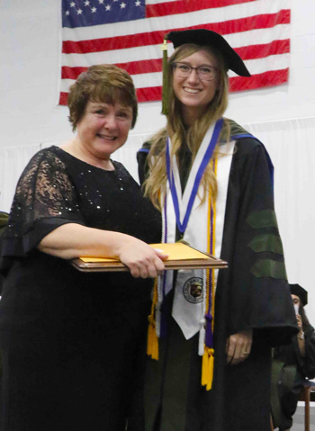 Mary Ann Blessing, daughter of Lloyd L. Gregory, presents Laura Neubauer with the Gregory Outstanding Graduate Award. The award comes with a plaque, a $10,000 check and an expectation that the recipient glorify God through the practice of pharmacy.