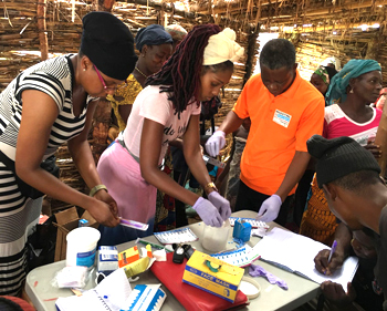 Dr. Nakisha Kinlaw, left, and doctor of nursing practice student Trenae Garibaldi, center, organize supplies for a medical outreach event in Egbe. They provided dental screening, HIV testing, lab testing, medical assessments and medication to 150 people living in rural villages.