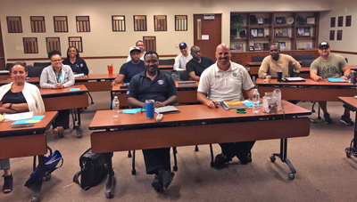 Boynton Beach employees who are pursuing their organizational leadership degrees gather for class in a city fire station. Through a partnership with the University, they are able to take core classes in the degree program at the fire station with their colleagues.