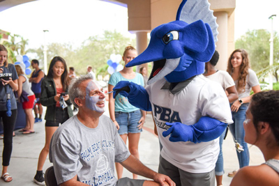 Photo: A dad gets his face painted by Sailfish Jack before a women's volleyball game during Family Weekend in 2017.