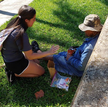 A nursing student distributes supplies and speaks with a man during a homeless outreach event at a West Palm Beach park.