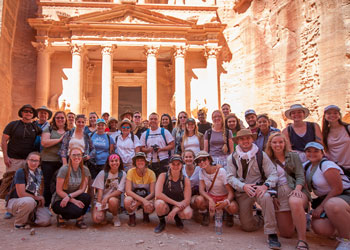 "Students and their professors pose for a photo while exploring the ""rose-red"" city of Petra in Jordan. The city is carved out of the rock of the cliffs that surround the valley."