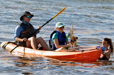 Dr. Angela Witmer's husband, Dr. Archie Ammons, paddles in the back of a kayak while student Amberlyn Stuart sits in the front. Student Sierra King is in the water. Stuart is working with Witmer to conduct underwater fish surveys. Photo by Dr. Witmer.