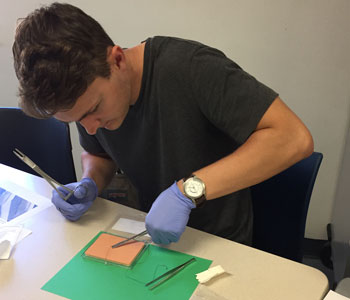 Tanner Young, a senior exercise science major, practices his stitching technique during a suturing lab in Dr. Cori Thompson's general medical conditions course. The course offers students instruction that is normally only given at the graduate level.