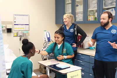 "A student from L.C. Swain Middle School's Pre-Medical Sciences Academy takes her classmate's temperature under the supervision of PBA student nurses Paige Phares and Christopher Kilburn in the nursing lab for ""A Day in the Life of a Nurse"" on Friday, Oct. 8, 2019. The visit was through the Nursing Consortium of South Florida."