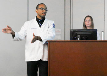 Ian Clarke presents a proposal for hospitals to hire pharmacists to provide at-home medication counseling in order to lower readmission rates and reduce penalties. Teammate Isabelle Serbulescu listens.