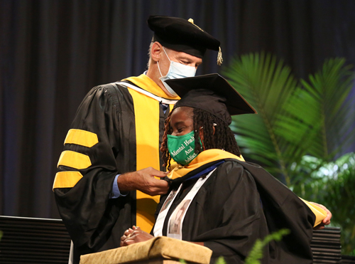 A student who earned her Master of Science in mental health counseling receives her hood. The hood represents the wearer's degrees and institutions.