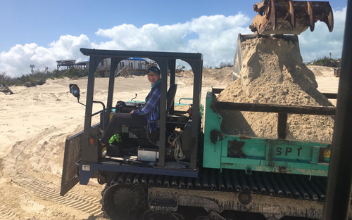 Abby Phillpot drives a track truck rebuilding a dune on the island of Guana Cay.