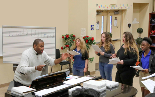 Sterling Frederick '95 directs his Boynton Beach Community High School choir during an after-school rehearsal.
