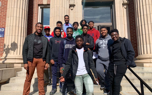 Emmanuel McNeely poses for a photo with students that he spoke to as part of the Dr. M.D. project. He wants young Black students to see that a medical career is possible for them.