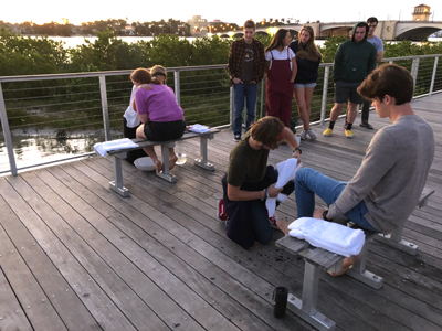 Steering Committee Co-Directors Libby Aaron (left, seated and wearing pink) and Nate Olver (far right) have their feet washed in a sunrise ceremony along the waterfront in February.